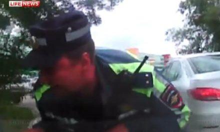 Escapa de un control con un policía en el capó